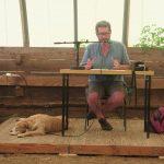 Jean-Chridstophe Goddard donnant une conférence avec un chien couché à ses pieds