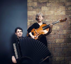 Vincent Lhermet à l'accordéon et Marianne Müller tenant sa viole de gambe comme une guitare, posant devant un mur moitié bleu moitié en brique.