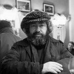 le musicien pablo cueco photographié en noir et blanc par Photo Milomir Kovacevic à la table d'un bistrot