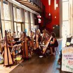 ensemble de harpistes jouant d'un lieu très éclairé par des baies vitrées